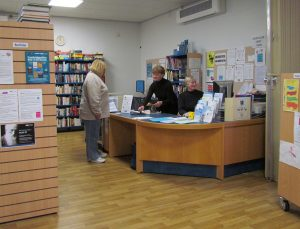 Staff at a desk talking to a visitor at in the library at the Swifts in Fulbourn